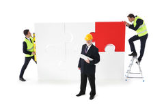 Workers assmebling puzzle Stock Photo