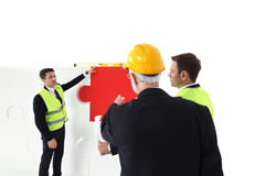 Workers assmebling puzzle Royalty Free Stock Images