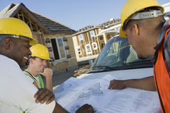 Workers With Blueprint At Discussion Stock Photo