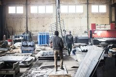 Workers in boots walk inside the industrial factory royalty free stock image
