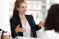 Young business woman talking with staff at formal meeting briefing. Workers brainstorming at meeting, focus on young attractive cheerful team leader telling stock photography