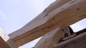 Workers build and stack boards wooden house. Clip. Workers install beautiful wooden beams on construction site of house. Wooden house in mode of construction stock video footage
