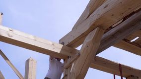 Workers build and stack boards wooden house. Clip. Workers install beautiful wooden beams on construction site of house. Wooden house in mode of construction stock footage