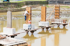 Workers building bridge foundation across lake Stock Photography