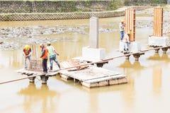 Workers building bridge foundation across lake Stock Image