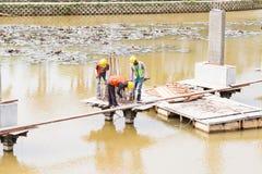 Workers building bridge foundation across lake Royalty Free Stock Image