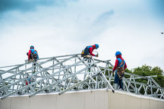 Workers are building a steel roof frame on high. Stock Photo