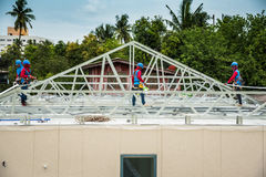 Workers are building a steel roof frame on high. Stock Photos