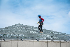Workers are building a steel roof frame on high. Stock Image