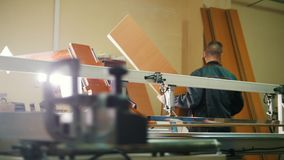 Workers carpenters are cutting wood on electric saw at furniture factory stock video