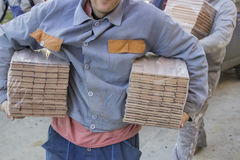 Workers carries packages of beech wood profiles Royalty Free Stock Image