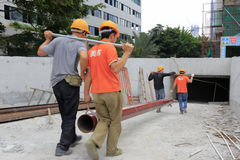 Workers carry large steel pipe. Four construction workers carry large steel pipe in building site, shenzhen city, china stock images