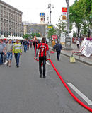 Workers carry the long red cable in Kiev, Stock Image