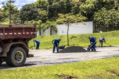 Workers carry out maintenance and cover the holes of a street in the city of Curitiba. Curitiba, Parana, Brazil, June 09, 2016. Workers carry out maintenance and stock photo
