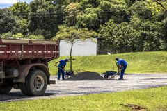 Workers carry out maintenance and cover the holes of a street in the city of Curitiba. Curitiba, Parana, Brazil, June 09, 2016. Workers carry out maintenance and royalty free stock photo