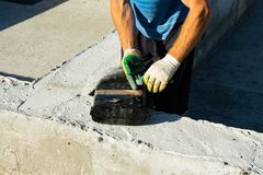 Workers carry out waterproofing of the Foundation for the construction of a wooden house. Copy paste stock photos