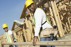Workers Carrying Boards At Construction Site Royalty Free Stock Photography