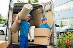 Workers Carrying Carpet And Cardboard Boxes. Two Male Workers Carrying Carpet And Cardboard Boxes In Front Of Van Stock Photography