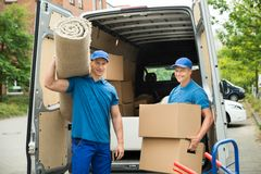 Workers Carrying Carpet And Cardboard Boxes Royalty Free Stock Images