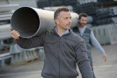 Workers carrying rubber tube pvc flex pipe. Carrying stock photography
