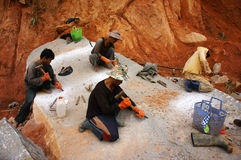 Workers carve out large rock  by hammer and splitter Stock Images