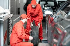 Workers changing wheels at the car service. Two car service workers in red uniform changing wheel of a sport car at the tire mounting service royalty free stock photos
