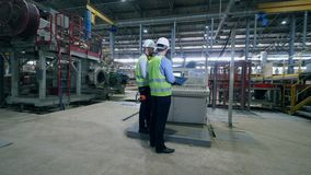 Factory male engineers in a modern factory. Workers check factory machines at a modern industrial plant. stock video footage