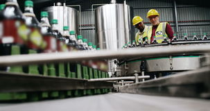 Workers checking bottles on production line stock footage