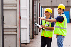 Workers checking containers. Smiling warehouse workers checking open containers before loading Royalty Free Stock Image