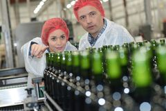 Workers checking conveyor bottles belt in factory Stock Images