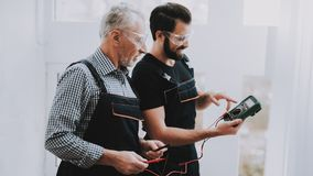 Workers Checking Device in Hands in Repair Shop. Worker with Tools. Computer Hardware. Young and Old Workers. Modern Devices. Digital Device. Wooden Table stock images