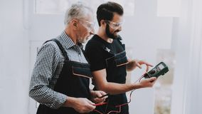 Workers Checking Device in Hands in Repair Shop. Worker with Tools. Computer Hardware. Young and Old Workers. Modern Devices. Digital Device. Wooden Table royalty free stock photos