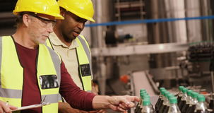 Workers checking juice bottles on production line stock video footage