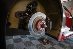 Workers are checking the rear brakes of a supercar in the garage stock photography