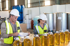 Workers checking records of oil bottles Royalty Free Stock Photo