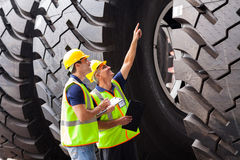 Workers checking tires. Shipping company workers checking industrial tires before exporting Stock Image