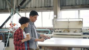 Workers talking in wood workshop, guy using tablet while girl is drinking coffee. Workers cheerful people are talking in wood workshop, guy is using tablet while stock footage