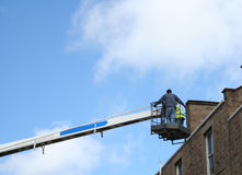 Workers in cherry picker. Inspecting roof royalty free stock photo