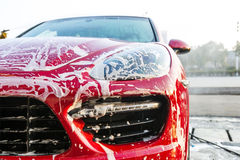 Workers clean the red car. Workers in the wash clean a red car Stock Photos