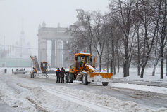 Workers clean from the road snow near the entrance to VDNKh in Moscow Royalty Free Stock Photo