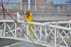 Workers cleaning a bridge with a high pression machine. BELGIUM, GHENT, 23 April 2015: Unidentified Workers cleaning a bridge with a high pression machine Stock Photography