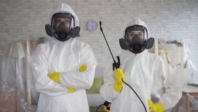Male and female workers in the cleaning service or the exterminator posing at the camera