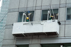 Workers cleaning skyscraper mirrored windows Royalty Free Stock Photography