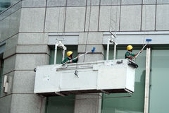 Workers cleaning skyscraper mirrored windows Royalty Free Stock Photos
