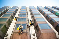 Workers cleaning the windows on the glass building Stock Photo