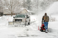 Workers clearing snow with blower and snow plow stock photo