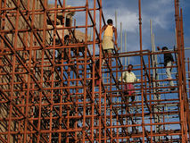 Workers climb iron scaffolding Royalty Free Stock Image