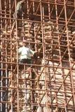 Workers climb iron scaffolding Stock Image