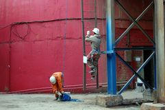 Workers climb a metal hanging ladder to paint the walls of an industrial building royalty free stock images
