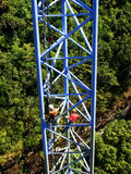 Workers climing supporting pole, Sky Bridge Stock Photo